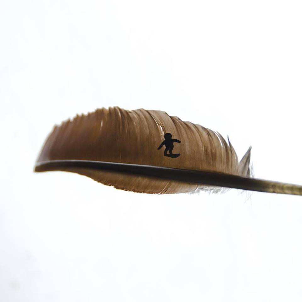 photo of a surfer made with a feather and construction paper by Kelly Crull